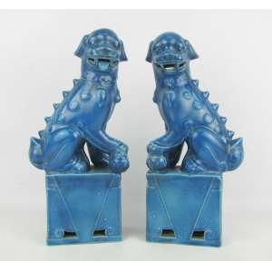 Par de estatuetas em porcelana na cor azul representando Cães fó. Uma com a língua quebrada. Alts. 26cm.