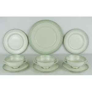 Dezoito peças em porcelana inglesa, com marca da manufatura Royal Doulton, com decoração de folhas no tom verde e detalhes em dourado, sendo 6 pratos rasos, 6 de sobremesa e 6 taças para consome com pires.