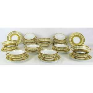 Quatorze taças com pires para consomé, em porcelana francesa de Limoges, decoradas com bela pintura em ouro brunido com folhagens e flores. Med. taça 4,5x15x12 cm. Diam. pires 16,5 cm.