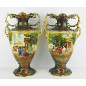 Par de vasos em faiança inglesa policromada e decorada com cena de babuínos de um lado e do outro com flores. Alças vazadas. Detalhes em dourado. Alt. 42 cm.