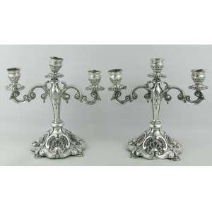 Par de candelabros estilo D. João V, em prata portuguesa, contraste Porto Águia, cinzelada em conchas, volutas e flores. Med. 23,5x24,5x16 cm. Peso 1.375 g.