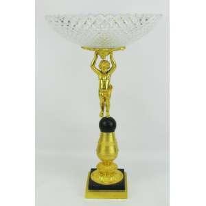 Excepcional e imponente centro de mesa em bronze banhado de dourado, na forma de criança sobre bola, sustentando belo prato em cristal alemão, com marca da Cristallerie Nachtmann, lapidado em losangos bisotados. Borda recortada. Med. 48,5x29 cm.