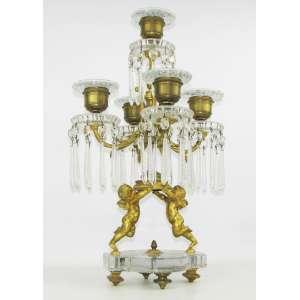 Baccarat - Excepcional candelabro francês para 5 velas em bronze e cristal, sendo este sustentado por dois querubins. Cristais e pingentes lapidados. Todos os braços apresentam bobeche com a marca da Cristallerie em relevo. Med. 50x29x29 cm.