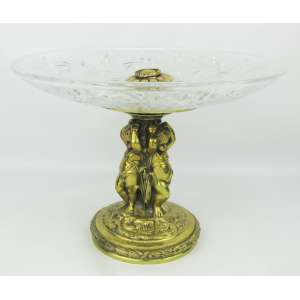 Belíssimo centro de mesa em bronze, com parte central formada por 3 meninos, que sustentam prato em cristal translúcido, tendo este lapidações de sulcos e rosetas. Base circular com trabalhos de folhas em relevo. Med. 24,5x33cm.