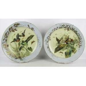 Belíssimo par de medalhões em porcelana francesa, com marca da manufatura Limoges no verso, decorados com pintura em policromia de folhagens com pássaros e borboleta. Detalhes em dourado. DIam. 45,5cm.
