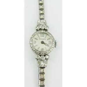 Relógio feminino em platina, ricamente cravejado com 50 brilhantes. Maquina necessita reparo. Peso total 20.9g. Comp. aberto 17,5cm. Este ítem não se encontra no local do leilão.