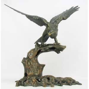 Imponente escultura em metal branco, patinado, representando Águia, estando esta sobre um tronco, com asas abertas. Minúsculas perdas na patina. Med. 67x70x32cm.