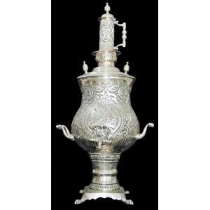 Grande Samovar Persa, Iran século XIX.Em metal espessurado a prata, cinzelado e burilado com em flores, folhas e volutas em baixo relevo. <br />Consta de inscrição no frontão. Alimentado a carvão.Alt. 84 cm.