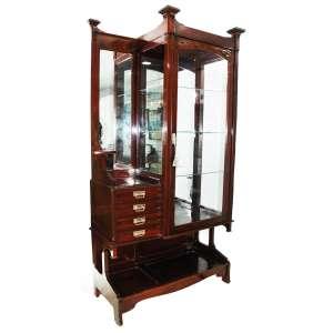 ART NOUVEAU (1890-1910) - Vitrine em madeira de Mogno maciço. Uma banda de porta envidraçada e espelhada. Apresenta na lateral direita quatro gavetinhas formando um platô e alçado com espelho, uma peanha de cada lado. Medidas: 231 x 121 x 50 cm.