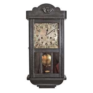 Relógio de parede alemão JUNGHANS, importado e comercializado pela joalheria CASA MASSON, PORTO ALEGRE RS. Caixa em madeira entalhada e porta com vidro. Mostrador em metal com marcas do tempo. Funcionando. Med. 53x25,5x14cm.
