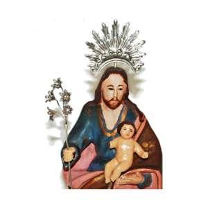 São José com menino - Imagem mineira, século XIX, em madeira entalhada, carnada e policromada. Olhos de vidro. Resplendor e bastão de lírios (Símbolo da pureza do casto José) em prata lavrada e filigranada. Medidas (com resplendor): 31 x 10 x 7 cm.