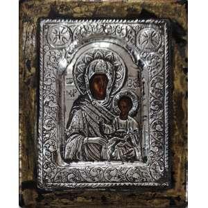 VIRGEM DE KAZAN. Ícone Grego com imagem em pintura sobre madeira e Oklad em prata de lei ricamente repuxada e cinzelada. Contraste para Grécia, Europa (final do séc. XIX Início do séc. XX). Teor gravado de 950 mls. Sobre moldura de madeira dourada. Medidas: 13 x 16 cm.<br /><br />HODEGÉTRIA: (em grego: Οδηγήτρια, que significa literalmente Ela que mostra o caminho [Jesus]; em russo: Одигитрия) é uma representação iconográfica da Teótoco (Virgem Maria) segurando o Menino Jesus num dos braços enquanto aponta para Ele como a fonte da salvação da humanidade, o Menino faz sinal de abençoar com a mão direita, leva na esquerda o rolo, pergaminho ouBola Mundi.<br /><br />DA DEVOÇÃO: Em 1579, uma menina de 9 anos de idade, de nome Matrona, cuja casa paterna desaparecera durante um incêndio nesse mesmo ano, sonhou com a imagem da Mãe de Cristo e ouviu uma voz dizendo que ela deveria ir buscar este ícone, que se encontrava nos escombros da casa incendiada. O ícone foi encontrado embrulhado num tecido antigo debaixo do fogão da casa destruída. Estava enterrado, provavelmente desde a época do domínio dos tártaros na cidade de Kazan, quando os fiéis eram obrigados a esconder a sua fé. O santo ícone foi com júbilo transferido para a igreja mais próxima -a igreja de S. Nicolau, e posteriormente para a catedral da Anunciação (Blagovechenskii) onde se consagrou pela cura de cegos.<br />
