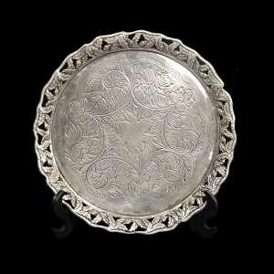 MICHEL KOURY - Salva em prata brasileira, decorada com galeria vazada em avelãs e guirlanda burilada e cinzelada ao centro. Base triploide com pés em pata de leão. Contraste do teor da prata 833 e marca de prateiro de São Paulo: M.K./P.L. Peso: 179 g. Medidas: 2,5 15 x 15 cm.