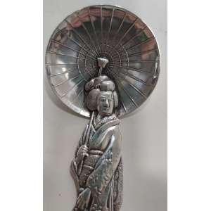 Impressionante miniatura em prata de lei japonesa, feita por volta de 1930 (período Showa).<br />Podendo ser usada como colher.<br />A alça tem a forma de uma Gueixa. <br />Sua sombrinha aberta forma a tigela da colher.<br />Marcado na parte de trás da haste: Sterling, 950.<br />Modelo do prateiro japonês Kichigoro Uyeda.<br />Peso: 38 g.<br />Medidas: 14 x 5,5 x 5,5 cm.<br /><br /><br />Em 1884, K.UYEDA, o predecessor do Joalheiro Uyeda, fundou uma joslheria na Rua Ginza Dentsu (antiga Minamisaeki-cho, Kyobashi-ku) em Tóquio. <br />Kichigoro Uyeda, aprendeu inglês por conta própria e começou um negócio com turistas. Eram pingentes, broches e brincos feitos com trabalhos manuais em um estilo tradicional que consiste em padrões desenhados com fio de prata fino e decorados com Cloisonné, chamado Hirado. Ainda produziu uma variedade de vasos de porcelana Satsuma, pratos, esculturas em marfim, talheres de prata ou ornamentos. <br />Diz-se que os clientes estrangeiros adoravam seus produtos.<br />Em 1922, abriu uma loja no Imperial Hotel Arcade, projetado por Frank Lloyd Wright, que recebia hóspedes de todo o mundo. Assim o nome de Ueda Joalheiro tornou-se amplamente conhecido no país e no exterior. Os livros de assinaturas de clientes incluem Babe Ruth, Joe DiMaggio, Sophia Loren, Charlton Heston, Gina Lorobrizzita, as estrelas de Frank Sinatra, MacArthur, Kissinger, Reischauer e outros dignitários.