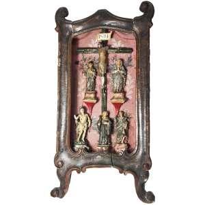 ORATÓRIO LAPINHA, MINAS GERAIS, Quadrilátero ferrífero, SÉCULO XVIII.<br />Crucificado ao centro. Da esquerda para direita: Santo Ivo, Nossa Senhora das Dores, ambos sobre peanha trapezoidal vermelha. ABAIXO: São Sebastião (sobre base rochosa), Santa Rita de Cássia, São João Evangelista (ambos sobre base marmorizada e faiscada). O CRISTO possui falta dos braços e das pernas abaixo dos joelhos. O madeiro é em galho verde rústico; está bem preservado o filactério.<br />Imagens esculpidas em talcita ou silicato de magnésio de cor leitosa, como uma porcelana, muito utilizada neste tipo de oratório, para dar mais graça, leveza, sobriedade, em conformidade com a plástica Rococó, em substituição das esculturas de madeira, pesadas e coloridas do Barroco.<br />A caixa é de talha rasa,pintura interna em Rosinhas de Malabar e plumagens, é finamente executada à têmpera sobre fundo rosado. Medidas: 39 x 20 x 8 cm.