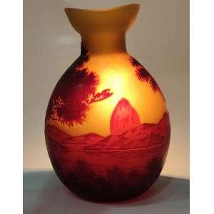 """Gallé<br />Vaso em pasta de vidro acidado. <br />Decoração em Camel <br />Representando paisagem do Rio de Janeiro. <br />Cores marrom e amarelo. <br />Med: 25 x 18 x 14 cm.<br /><br />SOBRE:<br />Não se pode evocar os anos de 1900, do Art Nouveau ou de Nancy sem evocar o nome de gallé.<br />O Mestre Vidreiro Emile gallé sempre quis que sua cidade natal fosse associada ao seu nome e à sua obra. Poucos anos antes de sua morte, lançou a Aliança Provincial das Indústrias de Arte, conhecida como Escola de Nancy de 1901). Objetivava reunir todos os artistas, artesãos e industriais.<br />A pasta de vidro é conhecida desde a antiguidade, mas nas mãos de gallé, que tambem foi um industrial, a produção passou de mais de um milhão de vasos durante sua vida.<br />gallé foi proprietário da empresa Emile gallé com mais de 300 funcionários.<br />O processo de decoração do vidro foi patenteado em 26 de abril de 1898 a foiapresentado no Salon du Champ de Mars em Paris no mesmo ano.<br />De 1894 a 1904, suas assinaturas em vidro são, na maioria das vezes, assinadas sem o primeiro nome do artista, gravados em camafeu ou em uma cavidade, com um único ou duplo curso.<br />Após sua morte até 1914, sua esposa decidiu usar a mesma assinatura para todas as produções, independentemente do cenário. A assinatura continuou de 1914 a 1936 pelos sucessores: Paul Perdrizet, Claude gallé e Emile Lang. O nome da empresa passou à: Maison gallé e depois Société anonyme des Etablissements gallé. A produção de peças durante a 1ª Guerra Mundial é estimada em 30.000 exemplares.<br />Entre 1896 e 1931 estima-se em 1 milhão a produção de peças """"gallé""""<br />Em 8 de maio de 1954 foi inaugurado Musée de l'Ecole de Nancy.<br />Hoje é, senão o maior nome do Art Nouveau, O maior vidreiro dos anos 1900."""
