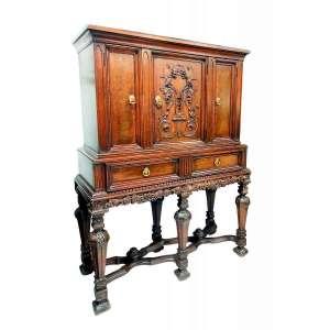 Antigo BUREAU DE GABINETE INGLÊS ESTILO WILLIAM & MARY (1685-1725).<br />Atribuído ao século XIX.<br />Madeira de nogueira. No Frontão simetricamente espelhado: pássaros e parras, cachos de uvas, rosáceas pendem de sinuosos ornatos esculpidos em baixo relevo.<br />Porta principal ladeada por duas estreitas forradas em rádica de raiz de nogueira, ogivas nas quatro colunas.<br />No segundo estágio, um gavetão falsamente bipartido. As parras se repetem na saia recortada. <br />Seis pernas em pilastras balaustradas. Possui travessas cruzadas entre as pernas, formando dois Xs de cada lado, encimadas por pinhas. MEDIDAS: 155x118x49cm.