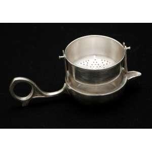 Antigo coador de chá com suporte para mesa, em prata 90 Eberle. Brasil, década de 1950. Medidas: 5 x 13 x 6 cm.