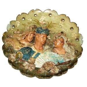 MAJÓLICA - Antigo medalhão em faiança espanhola, figurando toureiro ladeado por duas damas em alto relevo. Pintura manual, decoração floral, galeria vazada, pequena avaria na borda. Cerca de 1910. Diâmetro: 35 cm.