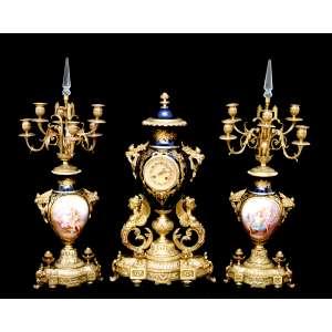TERNO DE RELÓGIO E DOIS CANDELABROS SÈVRES-FRANCE, século XIX.<br />RELÓGIO com base em efígies femininas aladas e ânfora de porcelana azul e ouro. Maquinário marcado : A.D. MOUGIN - DEUX MEDAILLS, datação estimada (1880 to 1900) FONTE: http://www.nawcc-index.net/Articles/Dean-french.pdf. MEDIDAS: 65 x 36 x 20 cm.<br />CANDELABROS com bojo em porcelana de SÈVRES, excepcional pintura manual no frontão BACO E ARIADNE e MARTE E VÊNUS. Paisagens na reserva posterior. Para cinco luzes, pináculo de cristal no centro, removível para limpeza. Alças à guisa de cornucópias de frutos e flores rematada por cortinados, pedestal encimado por par de pinhas. MEDIDAS: 66 x 29,5 x 29,5 cm.
