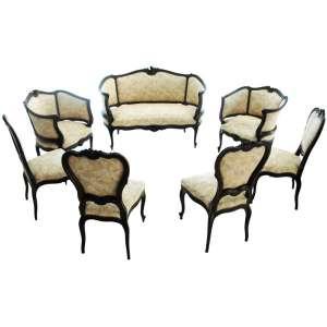 Antiga sala de estar estilo LUIS XV- ROCAILLE, século XIX. Consta de canapé, duas poltronas de braço e quatro cadeirinhas. Madeira de cedro maciço e escurecido. Estofamento com molas, no estado. Pés cabriolet, fina talha. Medidas: 97 x 140 x 57 cm.; 86 x 72 x 50 cm.; 92 x 50 x 47 cm.