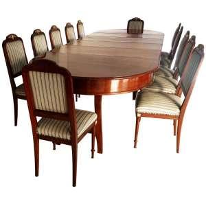 Antiga mesa de jantar para doze convivas, em MOGNO MACIÇO. Estilo inglês VITORIANO, século XIX. Quatro pernas torneadas, amarração em xis, e mais duas pernas de cavalete para total extensão. Ornamentos em bronze, polidos; ornatos no espaldar das cadeiras, rosetas e arremates nos flancos. Medidas mesa aberta: 80 x 365 x 130 cm. e 80 x 272 x 130 cm. Medidas mesa fechada: 80 x 174 x 130 cm. Medida das cadeiras: 100 x 44 x 43 cm.