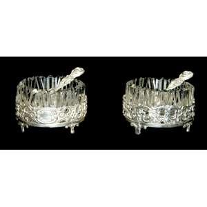 STERLING 925 GERMANY - Saleiro e pimenteiro de cristal lapidado e prata, base redonda assentada em quatro pés, varanda prata vazada e recortada com motivos fitomorfos e duas colheres de prata decoradas com folhas e flor. Medidas: 5 x 3,5 cm.