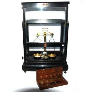 Balança analítica (laboratório- farmácia) - Record- Brasil, década de 1960. Completa em estojo de madeira envidraçada, uma gaveta, estojo com pesos. 48x41x25 cm.<br />http://www.iq.unesp.br/#!/extensao/museu-de-quimica/galeria-de-pecas/balancas/