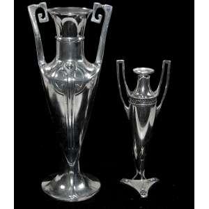 Lote com duas floreiras alemãs estilo Jugendstil (1890-1910). <br />Sendo uma W.M.F.: 21x8x8 cm. <br />Maior: 29x10x10 cm. 900 g. <br />Banho de prata refeito, perfeito estado.<br /><br />WMF foi originalmente chamado de Metallwarenfabrik Straub & Schweizer em 1900 era o maior produtor e exportador mundial de utensílios domésticos de metal, principalmente no estilo Jugendstil, ou Art Nouveau , projetado no WMF Art Studio sob orientação de Albert Mayer, escultor e designer, que foi diretor de 1884 a 1914 <br /><br />Conhecida como Jugendstil, termo alemão para estilo da juventude, é uma reacção à arte académica do século XIX, inspirado por formas e estruturas naturais de linhas curvas.<br /><br />Foi popular na Europa, mas influenciou global. O período em voga foi chamado de Belle Époque. <br /><br />Apesar dos estilos modernistas do século XX, foi importante movimento de transição entre o historicismo e o modernismo. É novamente, muito apreciado nos dias de hoje. <br /><br />Os monumentos art nouveau / Jugendstil são, atualmente, reconhecidos pela Organização das Nações Unidas para a Educação, a Ciência e a Cultura pois ilustram a transição do século XIX para o XX na arte, pensamento e sociedade.<br /><br />