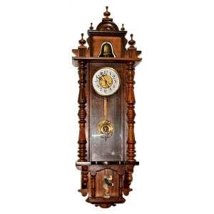 Raro relógio de parede, encimado por sino,no nicho inferior figura do Corcunda de Notre Dame, personagem do clássico de Victor Hugo (1831). Mostrador com figura de abelha, pêndulo com efígie feminina. Alemanha, século XIX.<br />Medidas: 140x44 cm.