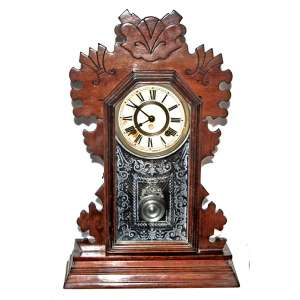 ANSONIA Clock Co. U.S.A. Modelo: Beaver, ca 1894.<br />57X39X12 cm.<br />De mesa ou parede. Caixa original em madeira de nogueira entalhada. Vidro original com gravação. Corda para 8 dias.<br />http://www.antiqueansoniaclocks.com/Ansonia-Model-0060.php