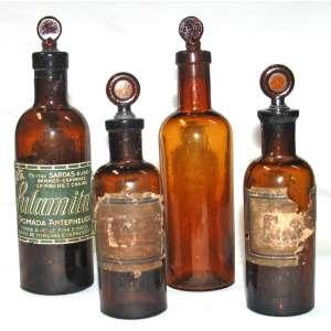 Lote (4) vidros âmbar de farmácia. Maior:21 cm. Menor:17 cm.
