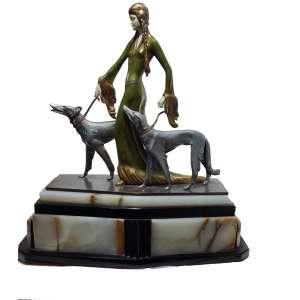 Otto Poertzel<br />Escultura em bronze e marfim,Art Déco, patinada, rosto primoroso, finamente esculpido em marfim.<br />Os aristocratas. Grupo figurativo de marfim pintado a frio e esculpido em marfim e bronze sobre uma base de ônix, criado por volta de 1925 pelo professor Otto Poertzel<br />ORIGEM: Alemanha <br />DIMENSÕES: 51 x 50 x 20 cm.<br /><br />O título Professor foi-lhe dado em 1913 pelo duque Carl Eduard, o último membro da família governante de Saxe-Coburg e Gotha. Provavelmente porque Poertzel foi um membro fundador da Coburg Art Association, e por suas associações acadêmicas.<br /><br />Pintura a frio é uma forma de aplicar cor a um bronze após o processo de fundição. Depois de frio, a patina é aplicada.<br /><br />O período Art Déco envolveu materiais de alta qualidade e acabamentos exóticos e raros. Na época, o marfim era considerado o melhor material para entalhes complexos das figuras que capturaram o sentimento glamoroso, positivo e otimista da época. Figuras dessa qualidade eram caras, mesmo naquela época por causa dos componentes de marfim.<br /><br />Estas figuras estavam na moda na época por sua aparência esguia. Em um livro de Alberto Shayo, tem uma foto de arquivo da Sra. Edmund Guy com cães Borzoi, no Casino de Paris, que se parece com essa escultura.