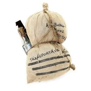 ARTUR BARRIO - Transportável n. 100. Garrafa de vidro, arado, tecido e corda. Assinado, datado 2002 e titulado. 50 x 30 x 24 cm. R$ 15.000 / 25.000