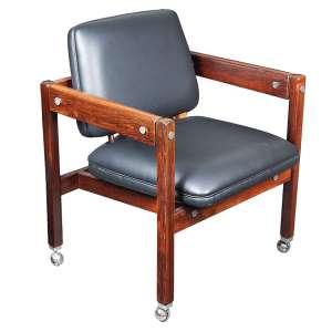 """SÉRGIO RODRIGUES - """"KIKO"""" Poltrona com estrutura de lei maciça, com rodízios cromados,assento e encosto estofados em espuma de poliuretano e revestidos em couro. 80 x 65 x 65 cm."""