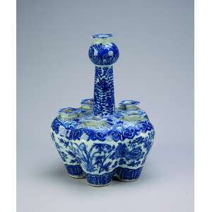 Tulipeiro de porcelana azul e branca, constituído de cinco vasos interligados entre si e um solitário, <br />elevado, à guisa de alça suspensória. 18 cm de diâmetro x 25 cm de altura. China, séc. XIX.