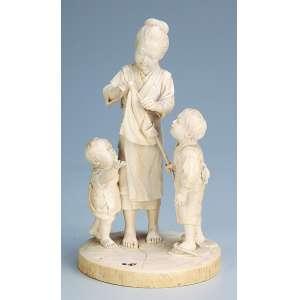 Grupo escultórico de marfim. Gueixa com estandarte e duas crianças. 20 cm de altura. <br />Assinado sob a base. Japão, séc. XIX.