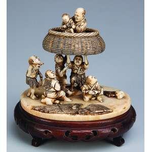 Pequeno grupo escultórico de marfim, constituído por cinco figuras, duas delas suspendendo <br />balaio com ancião e criança. Assinado. 10,5 x 10 cm de altura.