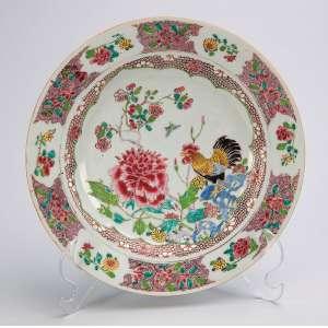 Prato raso de porcelana Cia das Índias, policromado, decorado em sua caldeira com crisântemo e galo. <br />21,5 cm de diâmetro. China, séc. XVIII.