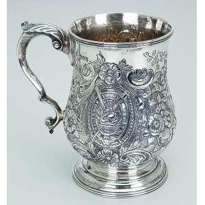 Caneca de prata repuxada e cinzelada, decoração floral em relevo. 13 cm de altura. <br />Contraste da cidade de Londres, com letra-data para 1891 e do prateiro Charles Belk. <br />Inglaterra, séc. XIX.