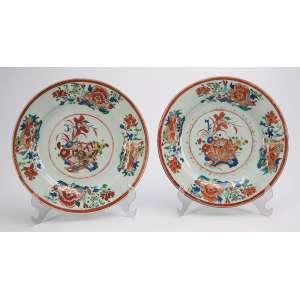 Par de requintados pratos de porcelana Cia das Índias, policromados e dourados. <br />Decoração floral. 23 cm de diâmetro. China, séc. XVIII.