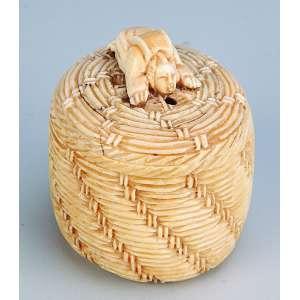 Escultura de marfim. Cena erótica dentro do balaio. <br />5 cm de diâmetro x 6 cm de altura. Japão, séc. XIX.