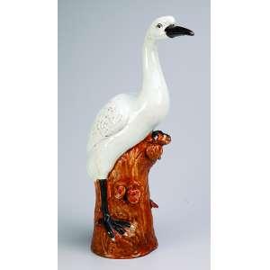 Garça de porcelana Cia das Índias, branca, pés e bico pretos. Apresenta-se sobre tronco. <br />40 cm de altura. China, séc. XIX.