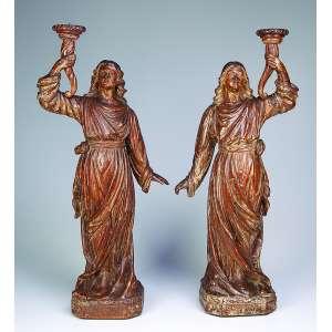 Par de anjos tocheiros esculpidos em madeira, apresentam resquícios de policromia. <br />Tochas em cornucópias. 66 cm de altura. Brasil, séc. XVIII.