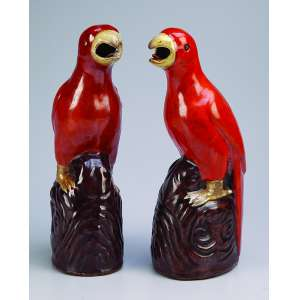 Par de pássaros de porcelana Cia das Índias, rouge-de-fer, bico amarelo. <br />Apresentam-se sobre rochedos. 28 cm de altura. China, séc. XIX.