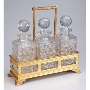 Tântalus com três garrafas de cristal de Baccarat em finíssimo suporte de bronze cinzelado <br />e dourado a ouro com chancela inglesa da fábrica Elkington & Co. Europa, séc. XIX.
