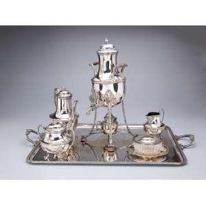 Serviço para chá e café de metal prateado, estilo neoclássico, composto de: samovar, <br />46 cm de altura, bule para café, açucareiro, cremeira, manteigueira e travessa <br />(62 x 95 cm). Europa, c. 1900. (apresenta alguns desgastes e pequenos amassados).