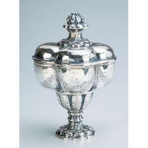 Bombonière de prata repuxada e cinzelada, bojo em gomos; pega da tampa em pinha. <br />Marca do teor 800. 18,5 cm de altura. Europa, séc. XX.
