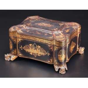 Caixa para chá de charão com ilustrações em chinoiserie dourado. Internamente dois recipientes de metal; <br />sobre quatro pés em cabeças de leões. 22 x 18 x 12,5 cm de altura. Japão, séc. XIX.