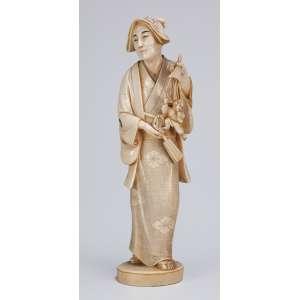 Gueixa com marionete e leque. Escultura em único bloco de marfim. 27 cm de altura. <br />Assinada sobre selo vermelho. Japão, séc. XIX.
